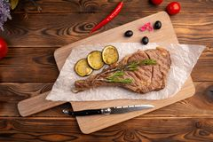 Grilled steak with lemon on a wooden background stock images