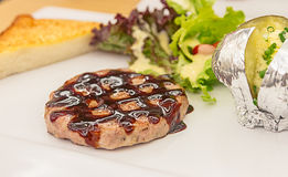 Grilled steak meat with salad of meal on background. Stock Images