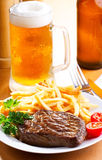 Grilled steak with mug of beer Royalty Free Stock Photos