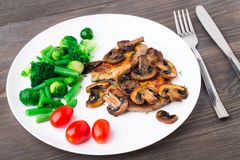 Grilled steak with mushrooms and vegetables Royalty Free Stock Photos