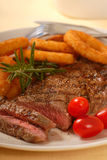 Grilled Steak with Onion Rings Royalty Free Stock Images