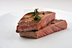 Grilled steak with organic rosemary. And bright background Stock Photography