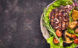 Grilled steak on plate above. Grilled steak with potatoes and tomato top view on grunge surface with copy space royalty free stock image