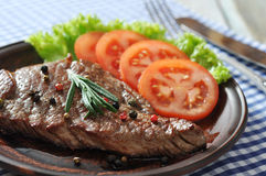 Grilled steak. On plate with tomatoes, spices and rosemary closeup royalty free stock photography