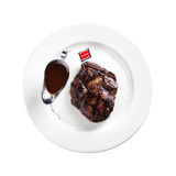 Grilled steak on a plate (white background). Grilled steak on a plate on white background Royalty Free Stock Photography