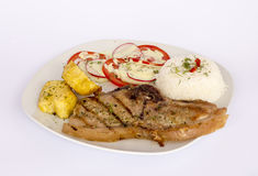 Grilled steak pork meat with salad, rice, potatoes, tomatoes. Royalty Free Stock Image