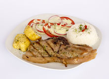 Grilled steak pork meat with salad, rice, potatoes, tomatoes served with a glass of chicha. Stock Photo