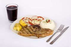 Grilled steak pork meat with salad, rice, potatoes, tomatoes served with a glass of chicha. Stock Photography
