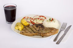Grilled steak pork meat with salad, rice, potatoes, tomatoes served with a glass of chicha. Stock Image
