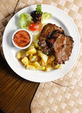 Grilled steak with potato chips stock images