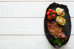 Grilled steak and potato, white wood, copyspace. Grilled steak and potato on white wooden background, flat lay, copyspace. Top view on clean table with black Royalty Free Stock Images