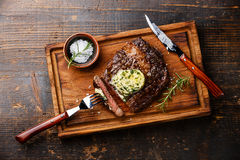 Grilled steak Ribeye with herb butter. On cutting board on wooden background Royalty Free Stock Images