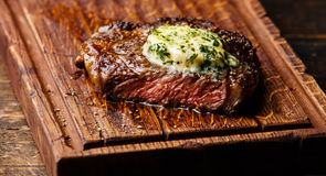 Grilled steak Ribeye with herb butter. Grilled Medium rare steak Ribeye with herb butter on cutting board serving size close-up Royalty Free Stock Photos
