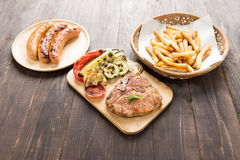 Grilled Steak with salad, french fries and sausage on wooden bac Stock Photo