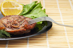 Grilled steak with salad and lemon on black plate with fork Stock Photos