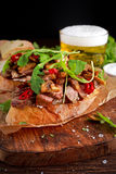 Grilled Steak Sandwich with mushrooms, goat`s cheese butter and rucola leaves on top. gold beer. royalty free stock photos