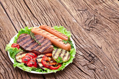 Grilled steak,sausages and vegetables. Royalty Free Stock Photos
