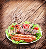 Grilled steak,sausages and vegetables. Stock Photos