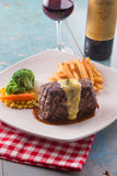Grilled Steak served with Hollandaise sauce. Fries, boiled corn, carrot, broccoli and red wine Stock Photography