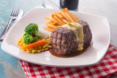 Grilled Steak served with Hollandaise sauce. Fries, boiled corn, carrot, broccoli and red wine Royalty Free Stock Photography