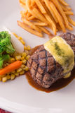 Grilled Steak served with Hollandaise sauce. Fries, boiled corn, carrot, broccoli and red wine Stock Images