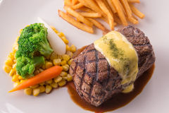 Grilled Steak served with Hollandaise sauce. Fries, boiled corn, carrot, broccoli and red wine Stock Image