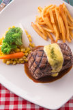 Grilled Steak served with Hollandaise sauce. Fries, boiled corn, carrot, broccoli and red wine Royalty Free Stock Photos