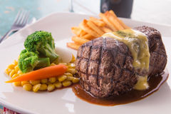 Grilled Steak served with Hollandaise sauce. Fries, boiled corn, carrot, broccoli and red wine Royalty Free Stock Images
