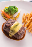Grilled Steak served with Hollandaise sauce. Fries, boiled corn, carrot, broccoli and red wine Royalty Free Stock Photo