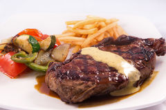 Grilled Steak served with Hollandaise sauce, fries, and stir fry / sauteed vegetable. In white background Royalty Free Stock Photography