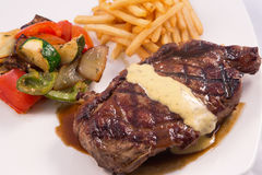 Grilled Steak served with Hollandaise sauce, fries, and stir fry / sauteed vegetable. In white background Royalty Free Stock Images