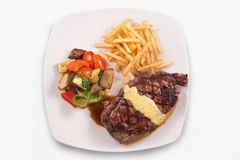 Grilled Steak served with Hollandaise sauce, fries, and stir fry / sauteed vegetable. In white background Royalty Free Stock Image