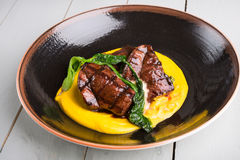 Grilled steak served with yellow humus Stock Photo