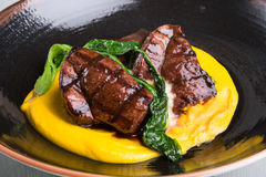 Grilled steak served with yellow humus Royalty Free Stock Image