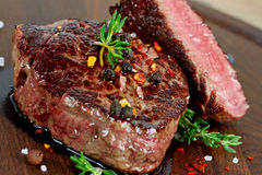 Grilled steak. With thyme on wooden board close up Royalty Free Stock Image