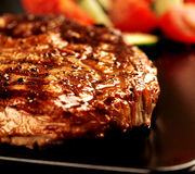 Grilled steak and vegetables on black plate close up Royalty Free Stock Image