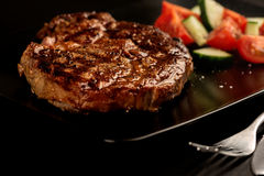 Grilled steak and vegetables on black plate with fork Royalty Free Stock Images
