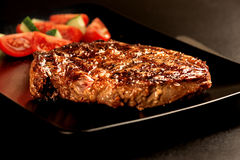 Grilled steak and vegetables on black plate macro Royalty Free Stock Photo