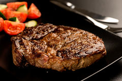 Grilled steak and vegetables on dark plate Royalty Free Stock Image