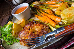 Grilled steak with vegetables and fried potatoes Royalty Free Stock Images