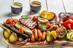 Grilled steak and vegetables with herbs on wooden board Royalty Free Stock Photos