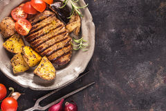 Grilled steak with vegetables on plate above. Grilled steak with vegetables and rosemary top view on grunge surface with copy space royalty free stock photography