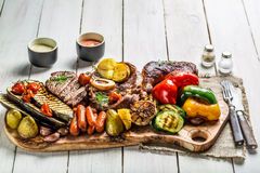 Grilled steak and vegetables with salt on wooden board Stock Photos