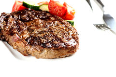 Grilled steak and vegetables on white plate close up Royalty Free Stock Images