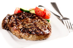 Grilled steak and vegetables on white plate with fork Stock Image