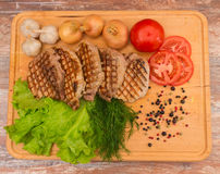 Grilled steak with vegetables on a wooden board Royalty Free Stock Photos