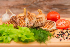 Grilled steak with vegetables on a wooden board Stock Photos