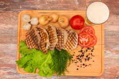 Grilled steak with vegetables on a wooden board. Stock Photo