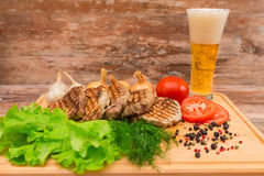 Grilled steak with vegetables on a wooden board. Royalty Free Stock Image