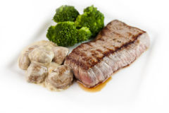 Grilled steak. On a white plate with mushroom sauce and broccoli Royalty Free Stock Photos